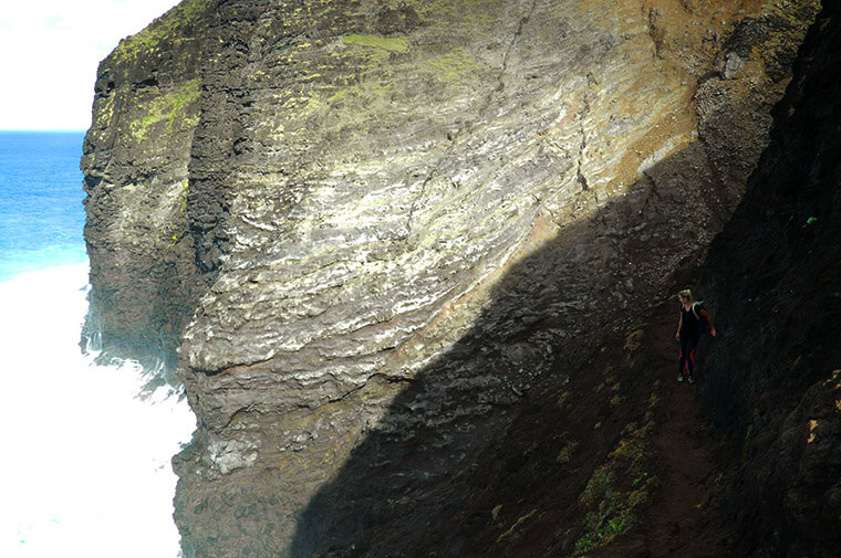 at the edge of the steep cliffs while conquering the kalalau trail in hawaii