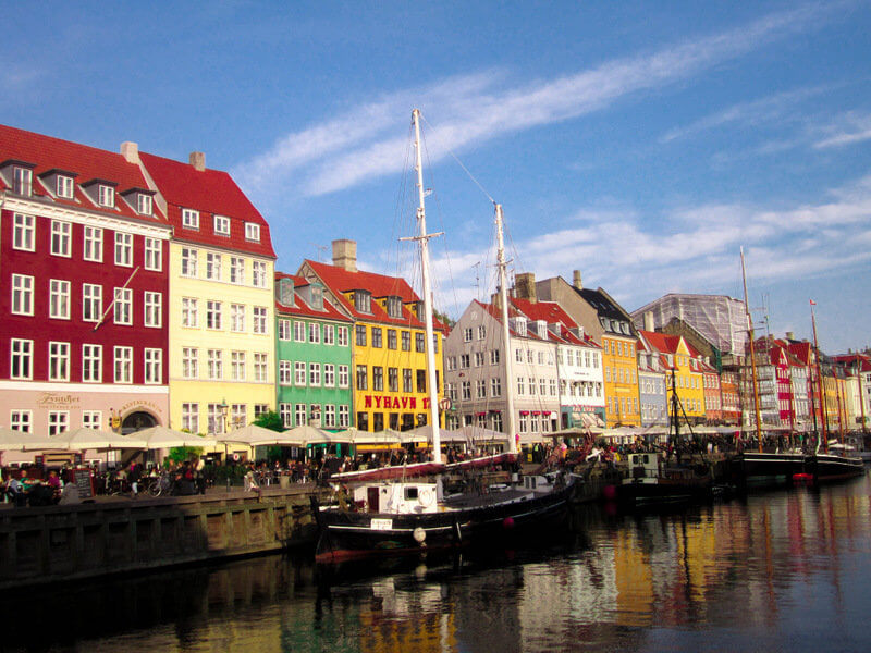 the famous nyhavn harbor in Copenhagen during summertime is a must see on your Copenhagen trip